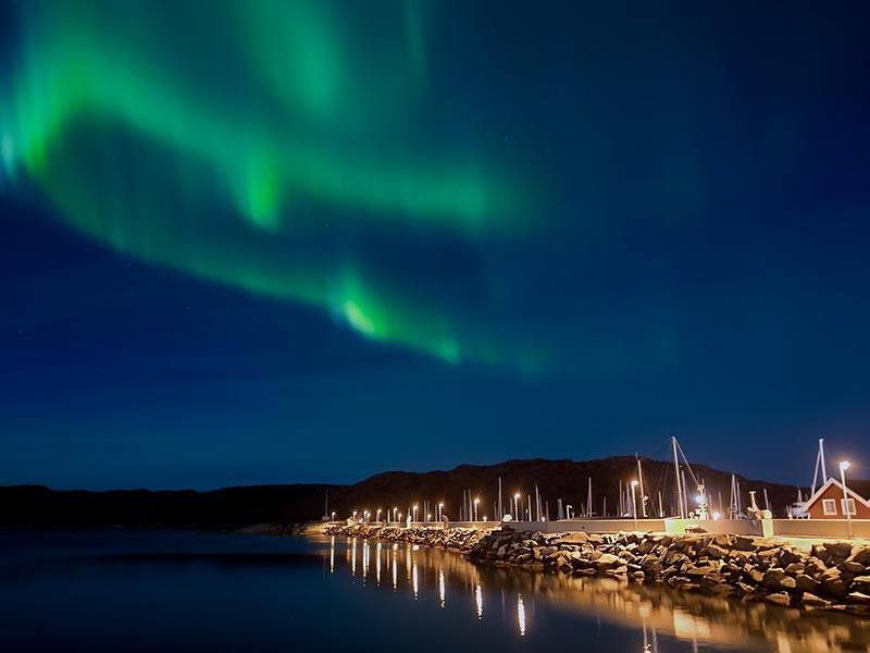 Northern Lights (Aurora Borealis) over a village in Norway